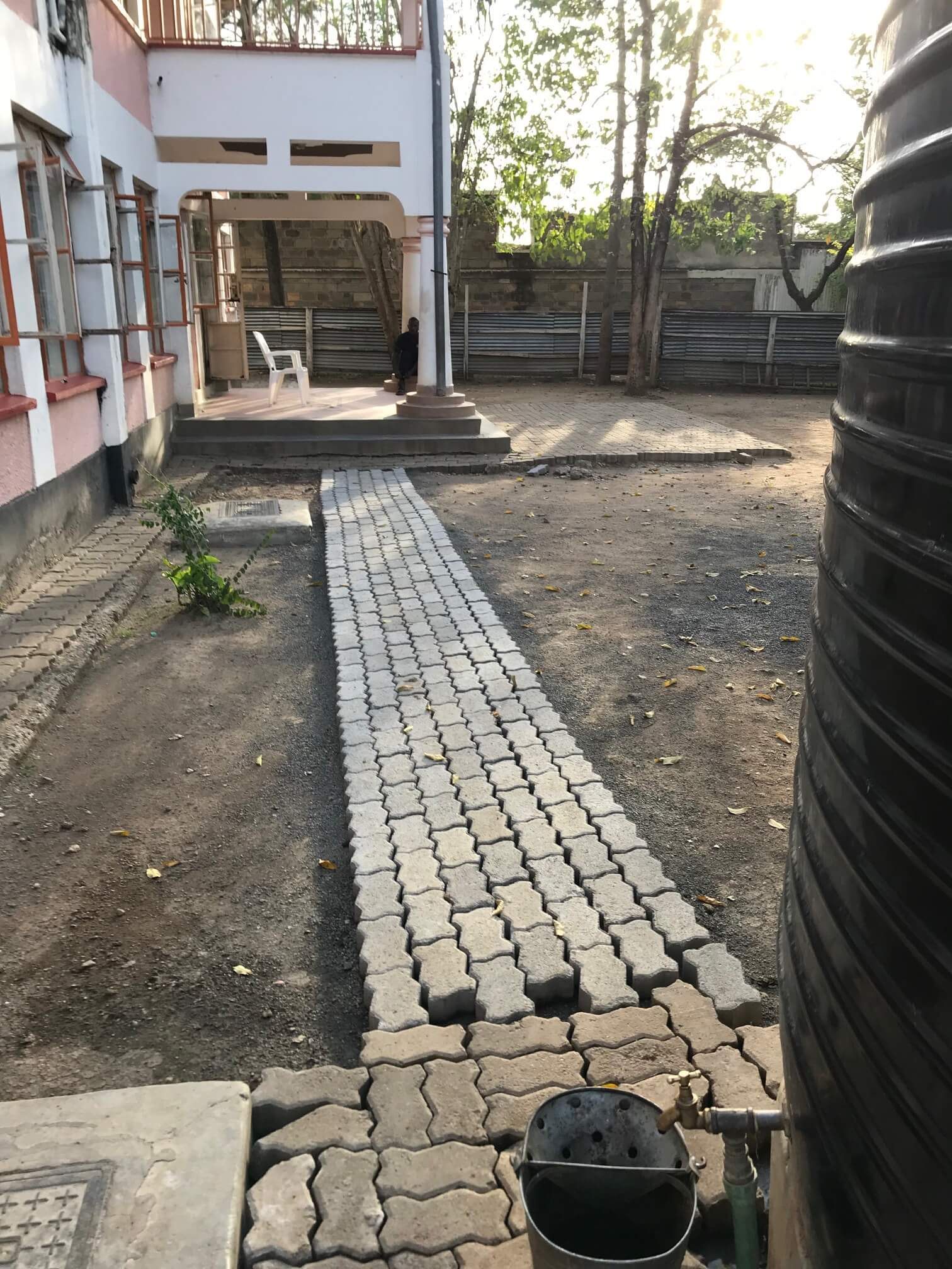 Humanity Home backyard paver walkway view 1